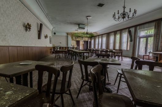 Old room with armchairs and tables in a guest house