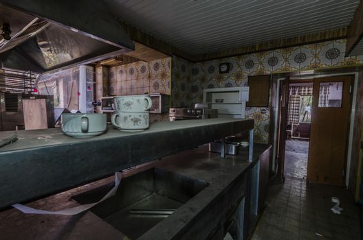 dishes and utensils in an abandoned hotel kitchen