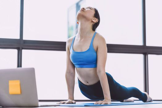 Asian woman practicing yoga from home with laptop when Covid19 outbreak and lockdown, healthy or Meditation Exercise, workout at home, coronavirus pandemic and quarantine,sports and healthcare concept
