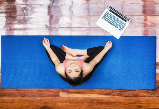 Top view Asian woman practicing yoga from home with laptop when Covid19 outbreak, healthy or Meditation Exercise, workout at home, coronavirus pandemic and quarantine, sports and healthcare in concept