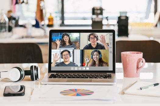 laptop with headphone, coffee cup, mobile phone and data graph document showing Asian Business people say hello with teamwork colleague in video conference when Coronavirus outbreak, Covid-19 pandemic