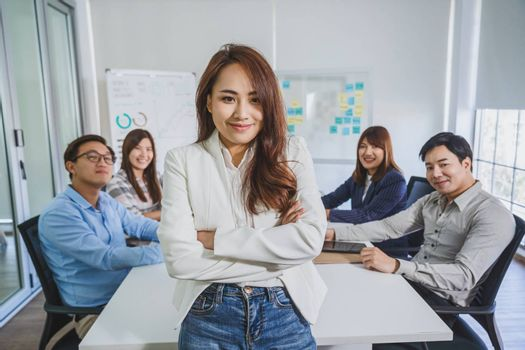 Portrait of Asian Business woman with Arms Crossed and standing over the group of colleague partner when brainstorming meeting at modern workplace, human resource and small business owner concept