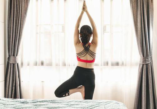 Back side of Asian woman practicing yoga from home in bedroom when Covid19 outbreak, healthy or Meditation Exercise, yoga workout at home, coronavirus pandemic and quarantine, sports and healthcare