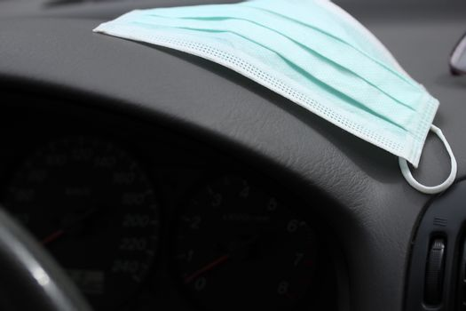 Protection face mask on the dashboard in the car