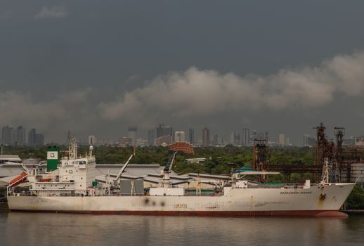 Bangkok, Thailand - Jun 17, 2020 : Cargo ships are floating over the Chaopraya river. They are waiting to be docked at pier.