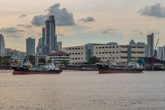 Bangkok, Thailand - 10 Jul 2020 : Two cargo ship parked in the middle of the Chao Phraya River with city at the background.