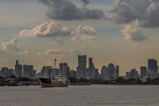 Bangkok, Thailand - 10 Jul 2020 : A cargo ship parked in the middle of the Chao Phraya River with city at the background. No focus, specifically.