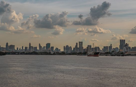 Bangkok, Thailand - 10 Jul 2020 : A cargo ship parked in the middle of the Chao Phraya River with city at the background.
