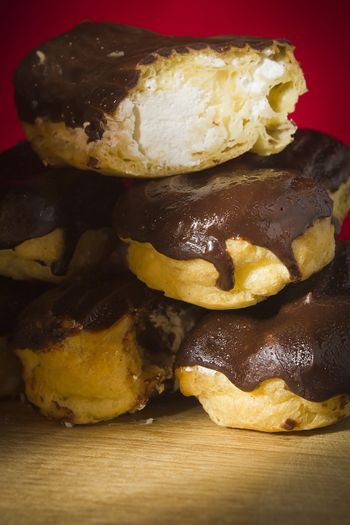 Eclairs with chocolate icing on a wooden table