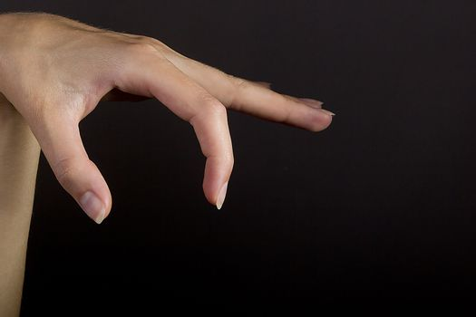 Female hand grab some item on black isolated background