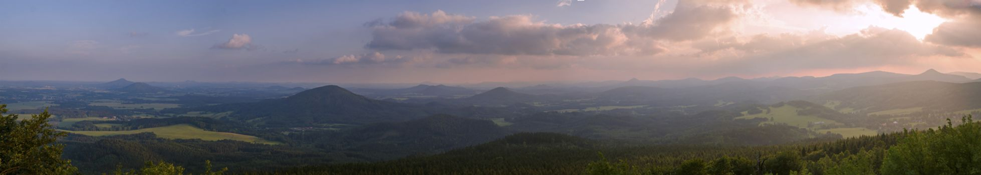 Lusatian Mountains (luzicke hory) wide panorama, panoramic view from Hochwald (Hvozd) mountain on czech german borders with blue green hills forest and pink cloudy sunset sky background