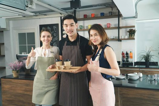 portrait Working together, coffee shop owner Asian mature women With barista, young Asian man, and Waitress young woman Caucasian people Cafe background of drink service Relaxing concept