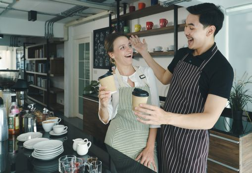 young Asian man talks with a Caucasian woman and laughed was happy. barista and waitresses discuss customer service in the coffee shop. The cafe work together, friendship, and relaxation concept.
