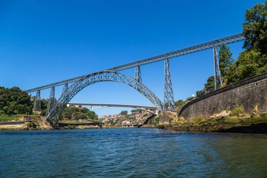 Maria Pia Bridge over the Douro river, Porto, Portugal. View from the water. Wrought iron railway bridge. One of the most popular touristic destinations.