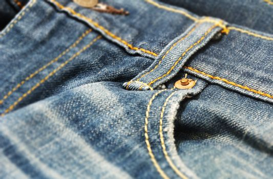 close-up view of the copper rivet on the pocket of a pair of denim trousers