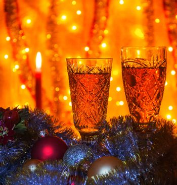 Some wine glasses of champagne lying Christmas balls and tinsel. On blurred background is visible burning candle.