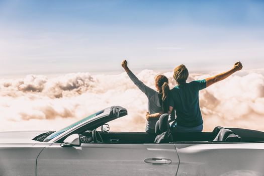 Happy car road trip couple freedom on summer travel vacation driving convertible sports car feeling excited winning free.