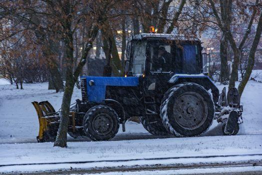 Traktor Balorus rensar snö från trottoaren under snöfall