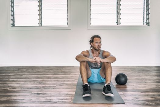 Gym workout man training floor exercises with weighted slam ball or medicine ball taking a break tired sweating thinking of disappointment