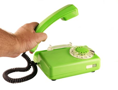 On a white background male hand holding a green telephone handset rotary dialer