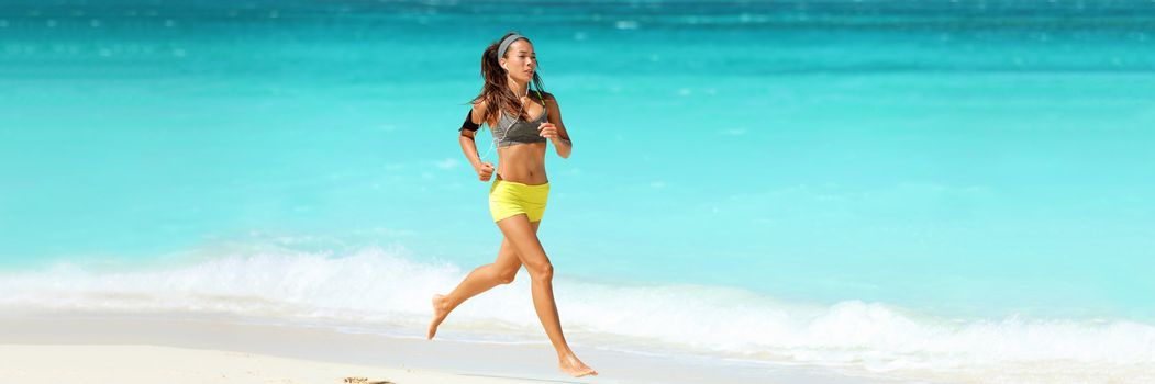 Healthy active lifestyle banner panorama. Fitness woman working out cardio running on beach wearing armband and earphones listening to phone music training jogging with blue background copy space.