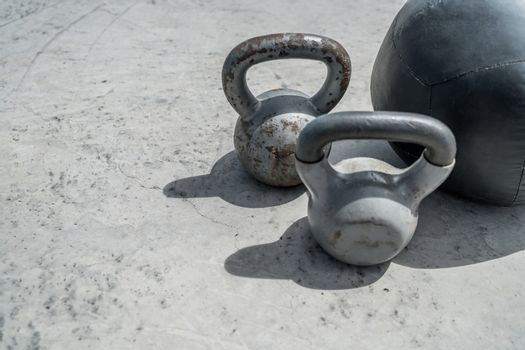 Gym kettlebell weight and medicine ball. Closeup of grunge background weights on concrete floor. Fitness and a healthy lifestyle