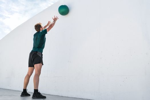 Strength training fit man cross training throwing medicine ball on gym wall at fitness centre. Workout bodyweight exercises using heavy weight ball. Overhead medicine ball throw plyometric exercise.