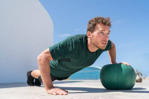 Pushup bodybuilder athlete strength training chest and shoulder muscles doing single arm alternating medicine ball push-ups floor exercises at outdoor gym.