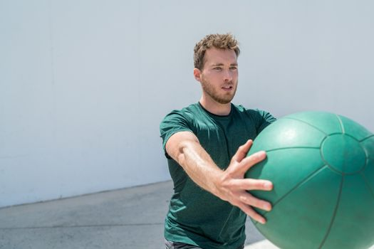 Medicine ball workout fitness man strength training arms doing deltoid front raise exercise for shoulder muscles at gym. Upper body workout with weight ball at fitness centre.