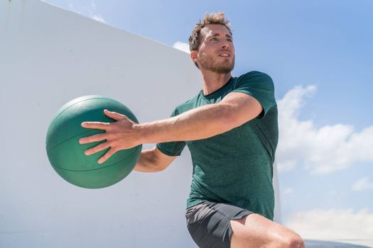 Fitness man training at gym working out legs and abs doing lunges twisting the torso for core workout with medicine ball weight. Crossfit body workout.