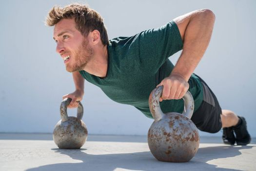 Fitness gym man doing pushups workout holding kettlebells for full extended push-ups floor exercises at outdoor gym. Athlete working out with bodyweight exercise.