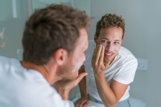 Man washing face with soap scrubbing exfoliation mask facial treatment looking in the mirror. Men taking care of skin, morning face wash routine for cleaning acne pimples