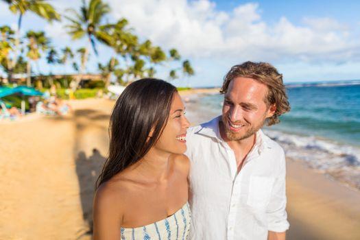 Hawaii travel beach couple laughing together happy on honeymoon vacation. People enjoying hawaiian sunset holidays.