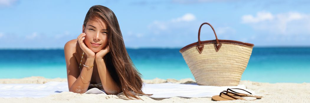 Woman relaxing on beach vacation summer holidays banner with copyspace on sky and blue ocean. Beautiful Asian girl lying down on towel with flips flops and beach bag tanning. Sun hair and skin care concept.