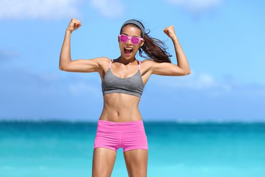 Strong fitness woman showing off muscular arms flexing biceps for fun on beach. Fit girl weight loss success. Power concept.