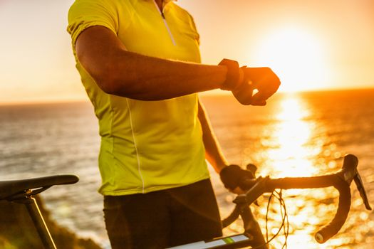 Smartwatch biking cyclist athlete using smart watch activity tracker gps during cycling training. Road bike sports man using his watch app for fitness tracking. Healthy lifestyle.
