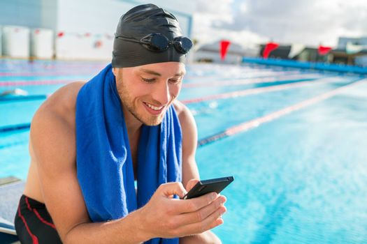 Swimmer man with swimming cap and goggles at pool using his mobile phone texting on smartphone app after training in outdoor pool. Happy athlete holding cellphone at fitness centre.