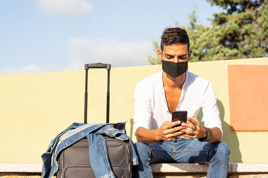 Young stylish caucasian man traveler with a black COVID protection mask using the smartphone sitting on a colorful bench with the denim jacket on a traveling bag - Coronavirus safe traveling concept