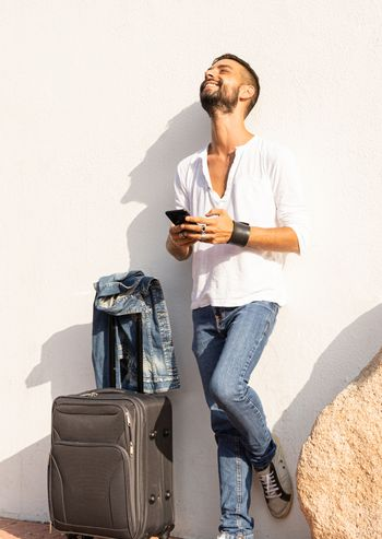 Happy young stylish caucasian man traveler smiling using the smartphone leaning against a white wall with traveling bag on the ground - Alwais connected concept - Solo male millenial traveller