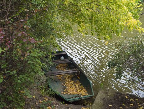 Old rowing boat with fallen leaves on the river bank in autumn with trees, countryside in golden afternoon light.