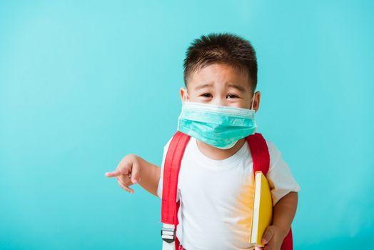 Back to school coronavirus Covid-19 education. Portrait Asian little child boy kindergarten wear face mask protective and school bag hold book before going to school pointing to side away, studio shot