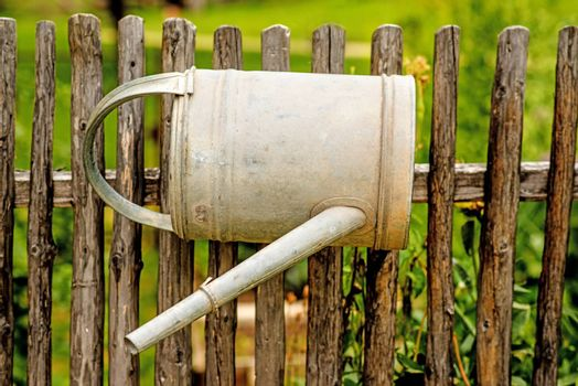 old watering a a wooden fence