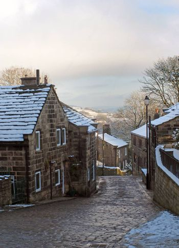 A scenic view of the main street in the village of heptonstall in west yorkshire with snow covering the old stone houses and pennine scenery visible in the background