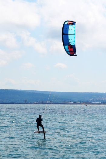 Varna, Bulgaria - July, 19, 2020: a man is kiting the sea on a sunny windy day