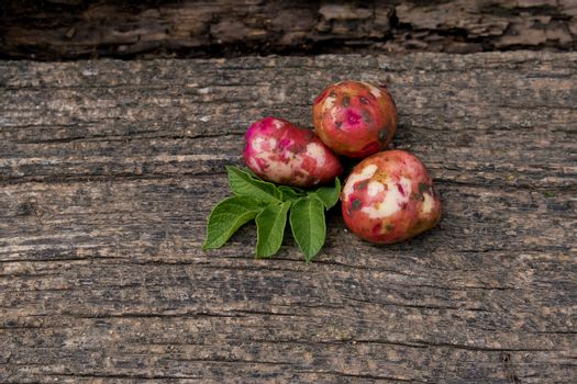 Raw young potatoes with foliage on a wooden background.