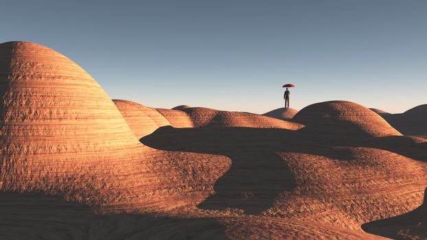 Man with red umbrella stands in rocky desert