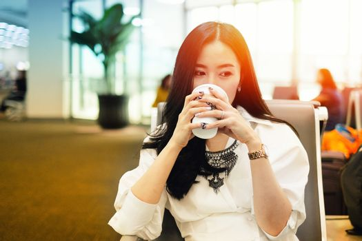 Woman drinking coffee while waiting to board at the airport