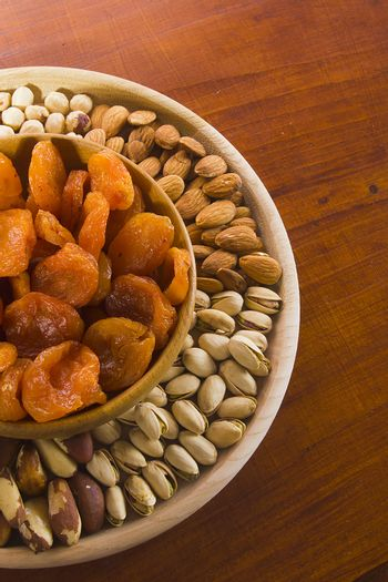 Set of nuts and dried fruits in a wooden bowl
