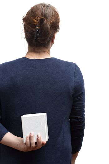 Woman with a gift behind her back on a white background