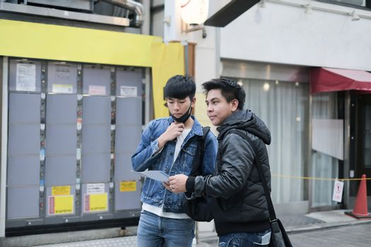 Two young handsome asian men travel in the city on walking street and searching the way to visit the best famous place